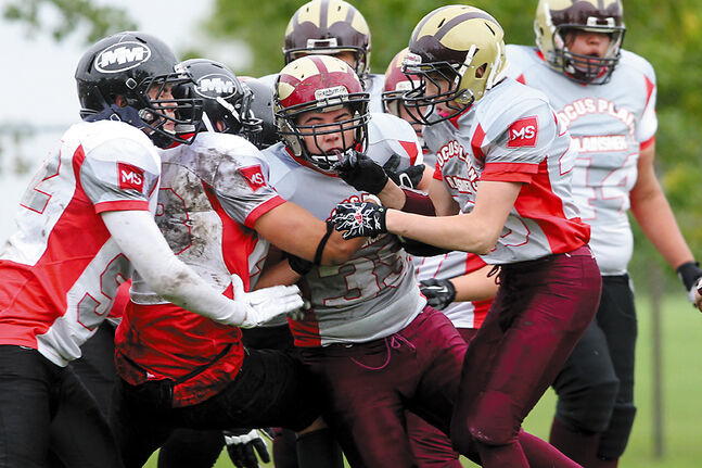 Running back Sam Esler (centre) of the Crocus Plainsmen tries to break through the Murdoch MacKay Clansmen defensive line during the Plainsmen's home opener in the Winnipeg High School Football League at the Crocus field on Thursday.