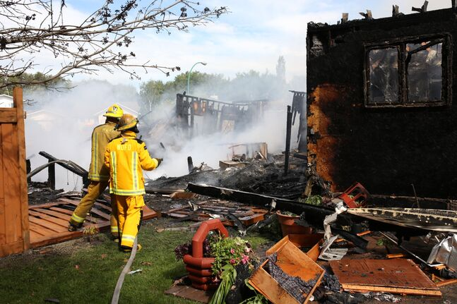 Firefighters battle a fire that consumed two homes on Thompson Place in Virden on Friday morning. Both homes were destroyed by the fire that was started by a gas explosion in one of the homes. (Tim Smith/Brandon Sun)