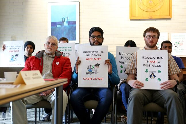 Protesters including Pruthvi Dhannapuneni (middle), an international student from India and president of the Brandon University International Students Organization, and Mark Klapheke (right), an international grad student from the United States, hold signs in opposition to the fees international students are charged to study at Brandon University, during a BU Board of Governors meeting at the university on Saturday.
