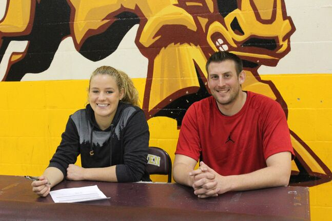 Erynn Buhr, left, is joined by Crocus Plainsmen varsity girls' basketball head coach Adam Hartman after signing her commitment letter to play hoops with the Dakota College-Bottineau Ladyjacks next season.
