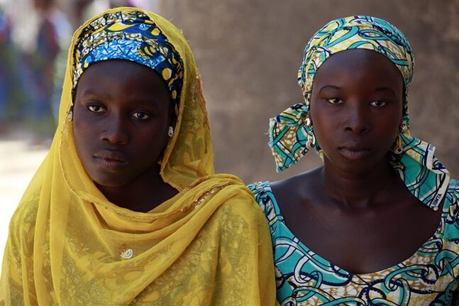In this photo taken Sunday, May 18, 2014, Joy Bishara, left, and Hadiza Fali, two of the school girls that escaped being kidnapped by Islamist extremists by jumping off a truck, pose in Chibok, Nigeria. More than 200 schoolgirls were kidnapped from a school in Chibok in Nigeria's north-eastern state of Borno on April 14. Boko Haram claimed responsibility for the act. (AP Photo/Sunday Alamba)