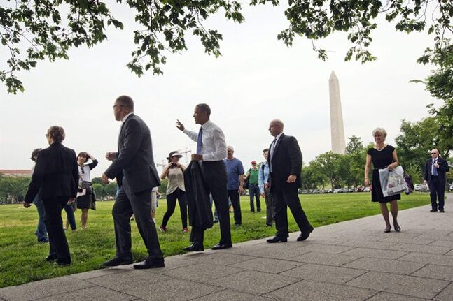 President Barack Obama, center, surrounded by members of the Secret Service, waves to tourists during his walk on the Ellipse in Washington, Wednesday, May 21, 2014. Obama walked to the Interior Department and back to the White House after signing a proclamation regarding the Organ Mountains-Desert Peaks National Monument. (AP Photo/Pablo Martinez Monsivais)