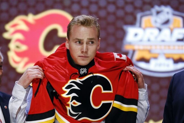 Sam Bennett pulls on a Calgary Flames sweater after being chosen fourth overall during the first round of the NHL hockey draft, Friday, June 27, 2014, in Philadelphia. (AP Photo/Matt Slocum)