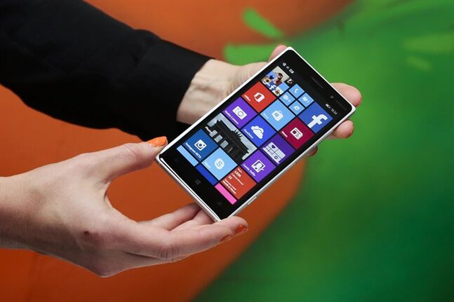 A woman shows the new Lumia 830 smart phone during a Microsoft Nokia presentation event at the consumer electronic fair IFA in Berlin, Thursday, Sept. 4, 2014. THE CANADIAN PRESS/AP, Markus Schreiber