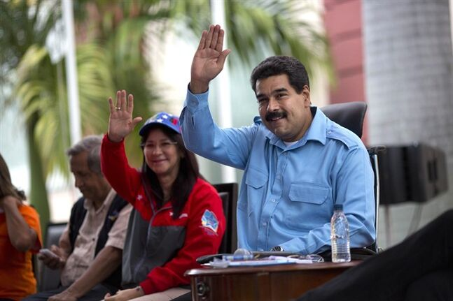 CORRECTS SPELLING OF FIRST LADY'S FIRST NAME - Venezuela's President Nicolas Maduro, right, and First Lady Cilia Flores wave to supporters at a pro-government rally with elderly people in Caracas, Venezuela, Sunday, Feb. 23, 2014. Maduro has been scrambling to squash an increasingly militant opposition movement after two weeks of anti-government protests against crime and inflation. (AP Photo/Rodrigo Abd)