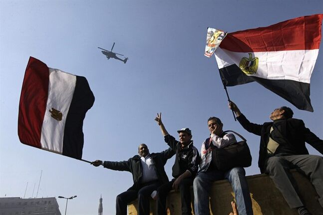 Egyptians wave national flags as they greet an army helicopter flying over Tahrir Square, the focal point of Egyptian uprising, in Cairo, Egypt, Saturday, Jan. 25, 2014. As Egyptians mark the third anniversary of their spectacular revolt against autocrat Hosni Mubarak in the name of democracy on Saturday, there has been a powerful sign of the country's stunning reversals since: letters of despair by some of the prominent activists who helped lead the uprising, leaked from the prisons where they are now jailed. (AP Photo/Amr Nabil)