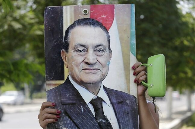 A supporter of former Egyptian President Hosni Mubarak holds his poster as she waits for his arrival at Maadi Military Hospital, following in his retrial in Cairo, Egypt, Wednesday, Aug. 13, 2014. Egypt's deposed President Mubarak on Wednesday denied that he ordered protesters killed during an uprising in 2011, in his first lengthy speech to a court as his year-old retrial draws to an end. (AP Photo/Amr Nabil)