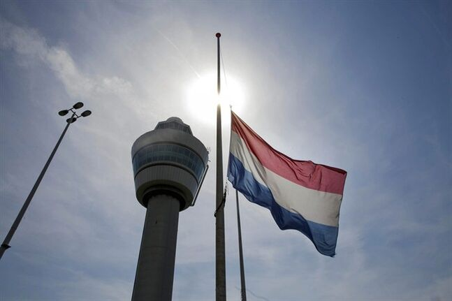 A flag flies half-staff near the traffic tower at Schiphol airport in Amsterdam, Friday, July 18, 2014. The attack on a Malaysian jetliner Thursday afternoon killed 298 people from nearly a dozen nations, more than half being Dutch, including vacationers, students and a large contingent of scientists heading to an AIDS conference in Australia. (AP Photo/Phil Nijhuis)
