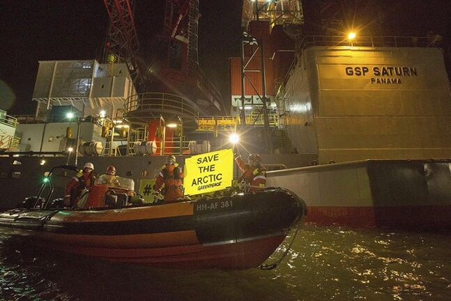 This image made available by environmental organization Greenpeace shows activists boarding a rig contracted by Russia's Gazprom in the port of IJmuiden, Netherlands, on Tuesday, May 27, 2014. Greenpeace said 30 activists in the Dutch port of IJmuiden on Tuesday boarded a rig contracted by Russia's Gazprom to drill in the Pechora Sea. Greenpeace said they were removed after five hours. (AP Photo/Bas Beentjes, Greenpeace) NO ARCHIVE