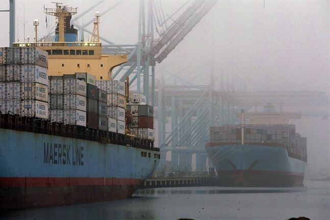 In this Dec. 5, 2012, photo, containers are unloaded from cargo ships at the Port of Los Angeles. THE CANADIAN PRESS/AP, Nick Ut