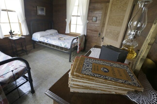 In this photo taken Friday, Aug. 8, 2014, elementery school books sit on a chest in a bedroom of a home where singer Johnny Cash spent much of his childhood in Dyess, Ark. Money and memorabilia from Johnny Cash's family and friends have helped historians restore a significant part of the Historic Dyess Colony, a government collective built to pull Depression-era families out of poverty. Cash's boyhood home, along with the colony's former headquarters, will open Saturday to reflect everyday life in a northeast Arkansas community built on once-sunken land. (AP Photo/Danny Johnston)