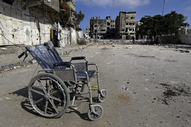 A wheelchair lies abandoned on a debris-strewn street amid the rubble of houses damaged by Israeli strikes in Beit Hanoun, northern Gaza Strip, Sunday, July 27, 2014. Hamas on Sunday agreed to observe a 24-hour humanitarian truce ahead of a major Muslim holiday after initially rejecting such an offer by Israel, as the two sides wrangled over setting the terms of a lull the international community hopes can be expanded into a more sustainable truce. (AP Photo/Lefteris Pitarakis)