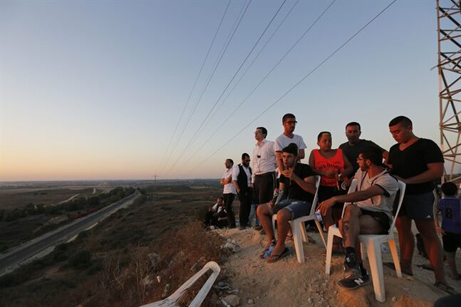 Israelis stand on a hill at the Israeli town of Sderot, overlooking the Gaza Strip, as they wait to watch Israeli forces' bombardment and rockets fired by Palestinian militants from inside Gaza towards Israel, Thursday, July 10, 2014. Israel dramatically escalated its aerial assault in Gaza Thursday hitting hundreds of Hamas targets, as Palestinians reported more than a dozen of people killed in strikes that hit a home and a beachside cafe and Israel's missile defense system once again intercepted rockets fired by militants at the country's heartland. (AP Photo/Lefteris Pitarakis)