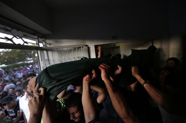 Palestinian mourners carry the body of their loved one, killed on an Israeli strike in Shijaiyah neighbourhood, out of the morgue of Gaza City's Shifa hospital, during the funeral, on Wednesday, July 30, 2014. Israeli strikes hit the crowded shopping area in Gaza City, hours after tank shells tore through the walls of a U.N. school crowded with war refugees Wednesday in the deadliest of a series of air and artillery attacks that push the Palestinian death toll above 1,300 in more than three weeks of fighting.(AP Photo/Lefteris Pitarakis)