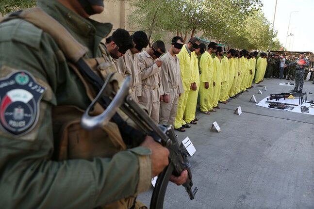 A member of Iraq's Special Weapons and Tactics Team stands guard as blindfolded suspected terrorists are displayed at the federal police headquarters in Basra, Iraq, Sunday, July 20, 2014. Iraq's SWAT arrested 21 suspected terrorists during recent security operations in Basra, according to police. (AP Photo/Nabil al-Jurani)