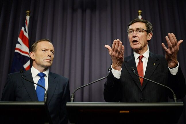 Prime Minister Tony Abbott, left, looks on as retired Chief Air Marshall Angus Houston, the head of the Joint Agency Coordination Centre, speaks to the media during a press conference at Parliament House in Canberra, Monday, April 28, 2014. Abbott and Houston announced Monday that the underwater hunt for the missing Malaysia Airlines jet will be expanded to include a massive swath of ocean floor that may take up to eight months to thoroughly search. (AP Photo/AAP Image, Lukas Coch) AUSTRALIA OUT, NEW ZEALAND OUT, PAPUA NEW GUINEA OUT, SOUTH PACIFIC OUT, NO SALES, NO ARCHIVES