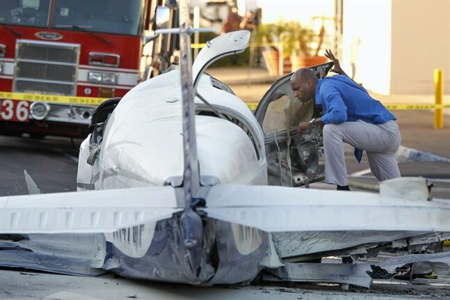 An aviation safety inspector looks inside the cockpit of a small airplane after it crashed in a shopping center parking lot Wednesday afternoon, July 30, 2014, in San Diego. One woman was killed and another seriously injured, a fire spokesman said. (AP Photo/UT San Diego, Hayne Palmour IV) NO SALES MANDATORY CREDIT TV OUT MAGS OUT
