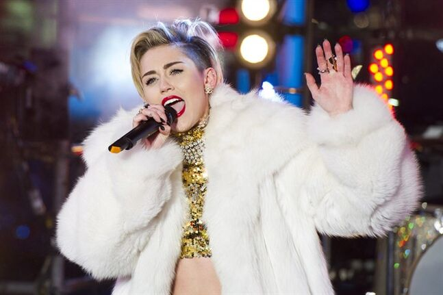 "In this Dec. 31, 2013 file photo, Miley Cyrus performs in Times Square during New Year's Eve celebrations in New York. Cyrus is kicking off her North American ""Bangerz"" tour Feb. 14, 2014, in Vancouver. ""Ren and Stimpy"" creator John Kricfalusi and LA contemporary artist Ben Jones have crafted videos to play during the 38 shows as Cyrus prioritizes singing over dance routines. (Photo by Charles Sykes/Invision/AP, File)"