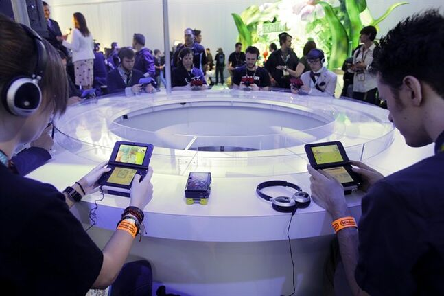 FILE- In this June 11, 2013 file photo, attendees play video games on the Nintendo 3DS at the Nintendo Wii U software showcase during the E3 game show in Los Angeles. The gaming company said Tuesday, May 6, 2014, it wouldn't bow to pressure to allow players to engage in romantic entanglements with characters of the same sex in the English version of