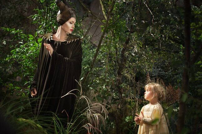 This image released by Disney shows Angelina Jolie as Maleficent, left, in a scene with her daughter Vivienne Jolie-Pitt, portraying Young Aurora, in a scene from the film,