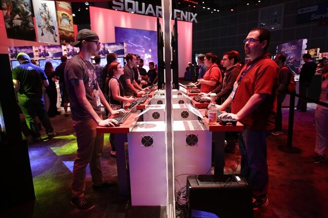 FILE - In this Thursday, June 12, 2014 file photo, people play a video game at the Square Enix booth at the Electronic Entertainment Expo, in Los Angeles. At last week's E3, video game developers hyped upcoming titles featuring assassins, super-soldiers, vigilantes and demon hunters. The lack of female protagonists at the expo highlighted an ongoing issue that continues to haunt the video game industry. (AP Photo/Jae C. Hong, file)