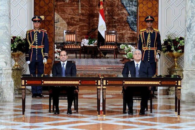 In this image released by Egypt's state news agency MENA, President Abdel-Fattah el-Sissi, left, and outgoing interim President Adly Mansour attend El-Sissi's inaugural ceremony at the Presidential Palace in Cairo, Egypt, Sunday, June 8, 2014. Egypt's newly sworn-in president called on his country Sunday to build a more stable future after years of turmoil and revolt, asking them to work hard so that their rights and freedoms could grow. Retired Field Marshal El-Sissi, the former military chief who ousted Egypt's first freely elected leader last July, addressed a ceremony held at a presidential palace in Cairo hours after he was sworn in by the Supreme Constitutional Court. (AP Photo/MENA)