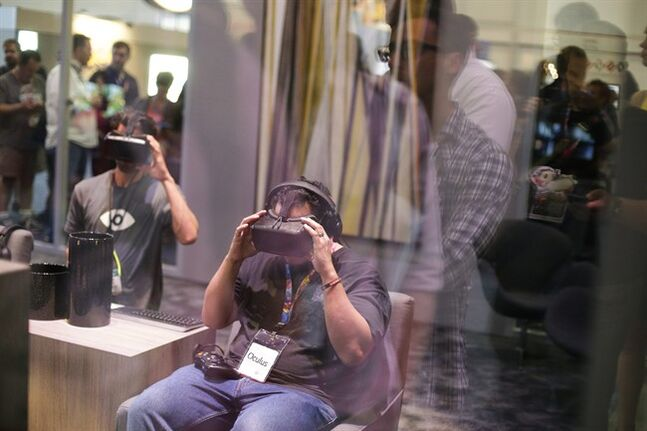 A man tries out the Oculus Rift virtual reality headset as show attendees wait in line outside the Oculus booth at the Electronic Entertainment Expo on Wednesday, June 11, 2014, in Los Angeles. (AP Photo/Jae C. Hong)