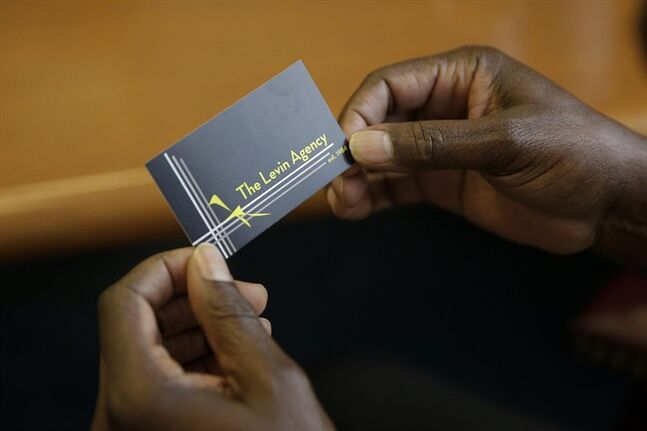 In this Wednesday, June 18, 2014 photo, Actor Abdoulaye N'Gom holds Hollywood talent agent Sid Levin's business card in Levin's office in Los Angeles. In a town where seemingly everyone wants to be a star, but very few look like James Franco or Scarlett Johansson, Levin is the talent agent who represents the people who look like the rest of us. (AP Photo/Jae C. Hong)
