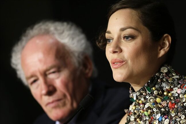 Director director Jean-Pierre Dardenne, left, listens to actress Marion Cotillard during a press conference for Two Days, One Night (Deux jours, une nuit) at the 67th international film festival, Cannes, southern France, Tuesday, May 20, 2014. (AP Photo/Thibault Camus)