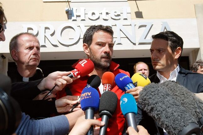 Former trader Jerome Kerviel, center, surrounded by his lawyer David Koubbi, right, and priest Patrice Bourrier, speaks during a press conference in front of his hotel, in Ventimiglia, Italy, near the French border, Sunday, May 18, 2014. The rogue trader facing three years in prison for one of the biggest trading frauds in history is appealing to the French president for mercy. Jerome Kerviel, who almost took down his bank, Societe Generale, with 4.9 billion euros in losses, has been on a months-long pilgrimage back to France after meeting the pope. He stopped his return just short of the border Saturday. Kerviel, convicted in 2010, insists he was the victim of a system that allowed his illegal trades as long as they made money. An appeals court threw out a fine equal to his losses, but upheld his prison sentence. Kerviel is supposed to report to start his sentence by Sunday or be considered a fugitive. (AP Photo/Claude Paris)