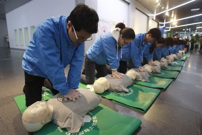 Relief squad members demonstrate CPR with dummies in Seoul, South Korea, on March 14, 2014. An anesthesiologist is suggesting recommendations on how to perform cardiopulmonary resuscitation or CPR may need to be changed. THE CANADIAN PRESS/AP, Ahn Young-joon