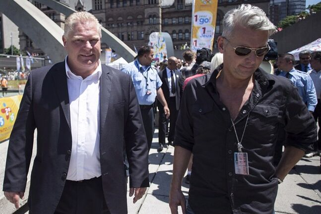Doug Ford, left, walks with Rob Ford's sobriety coach Bob Marier while attending the unveiling of the PanAm count down clock in Toronto on July 11, 2014. Mayor Rob Ford's brother has publicly apologized to Toronto's police chief for comments made earlier this month. Coun. Doug Ford's retraction of his comments comes two days after Chief Bill Blair filed a defamation notice against him. THE CANADIAN PRESS/Chris Young