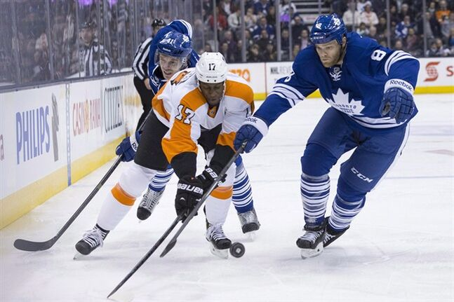 Toronto Maple Leafs' Tim Gleason (right) and Nikoai Kulemin (left) battle for the puck with Philadelphia Flyers' Wayne Simmonds during first period NHL hockey action in Toronto on Saturday March 8, 2014. The Leafs have placed Gleason on unconditional waivers for the purpose of buying him out. THE CANADIAN PRESS/Chris Young