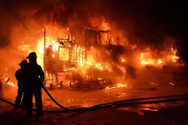 Fire engulfs a seniors residence in L'Isle-Verte, Que., early Thursday, Jan.23, 2014. A multimillion-dollar lawsuit has been filed against the Quebec town where 32 people died in a fire at a seniors' home last January. THE CANADIAN PRESS/Frances Drouin