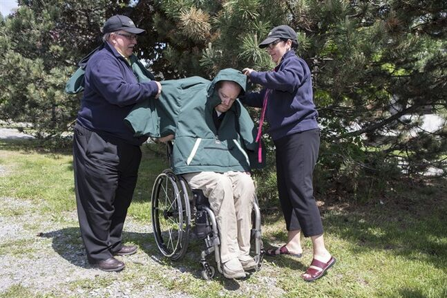 John Cook (left) and Jennifer Gallienne help Michael Johnson into a custom designed coat and outer wear for individuals confined to wheelchairs made by Koolway Sports, in Toronto on Monday May 26 , 2014. THE CANADIAN PRESS/Chris Young