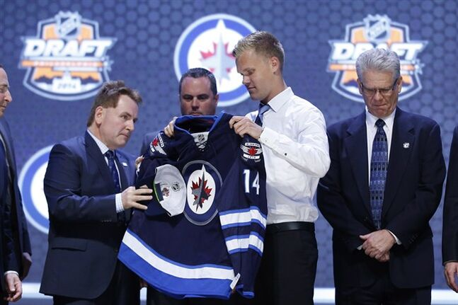 Nikolaj Ehlers pulls on a Winnipeg Jets jersey after being chosen ninth overall during the first round of the NHL hockey draft, Friday, June 27, 2014, in Philadelphia. The Jets have agreed to terms on a three-year, entry-level contract with 2014 first-round pick Ehlers. THE CANADIAN PRESS/AP /Matt Slocum
