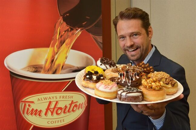 Actor Jason Priestley holds a plate of donuts in Oakville, Ont. on July 30, 2013. One lucky Canadian will have the chance to add their dream doughnut to the Tim Hortons menu and walk away with $10,000 as winner of Duelling Donuts contest, launched by the iconic bake shop today. Tim Hortons launched the contest last year, attracting 63,000 submissions. The idea came from a Jason Priestley cameo on