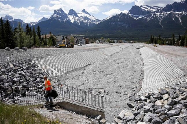 Work continues on flood mitigation along Cougar Creek Tuesday, June 3, 2014 one year after a devastating flood in Canmore, Alta. THE CANADIAN PRESS/Jeff McIntosh