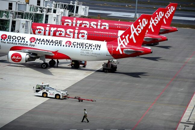 A ground crew man walks past a fleet of AirAsia's passenger jets in Sepang, Malaysia, Friday, May 9, 2014. THE CANADIAN PRESS/AP, Joshua Paul
