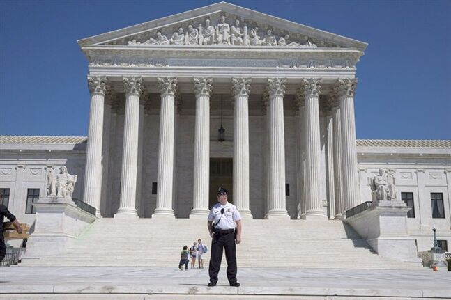A Supreme Court Police officer stands outside the U.S. Supreme Court in Washington April 26, 2014. THE CANADIAN PRESS/AP, Jacquelyn Martin