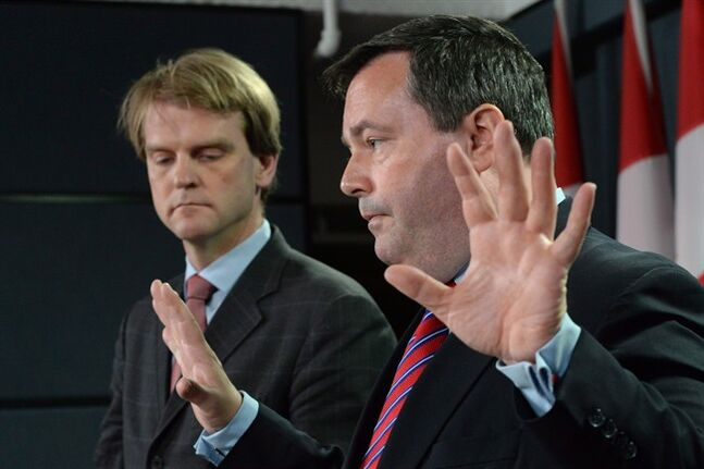Employment Minister Jason Kenney speaks as Immigration Minister Chris Alexander looks on in Ottawa on June 20, 2014. THE CANADIAN PRESS/Sean Kilpatrick