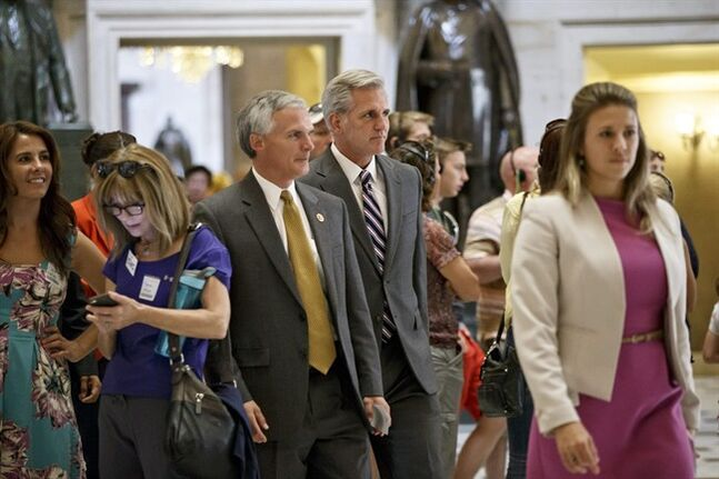 Incoming Majority Leader Rep. Kevin McCarthy, R-Calif., center, joined by Rep. Bob Latta, R-Ohio, center left,walk amid tourists at the Capitol on their way to the House chamber, in Washington, Wednesday, July 30, 2014. Republicans pushed a divided House Wednesday toward a campaign-season lawsuit against President Barack Obama, accusing him of deliberately exceeding the bounds of his constitutional authority. Democrats have branded the effort a political charade aimed at stirring up Republican voters for the fall congressional elections. (AP Photo/J. Scott Applewhite)