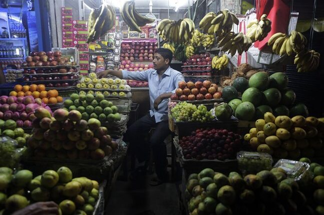A shopkeeper arranges fruits at a market in Gauhati, India, Friday, May 30, 2014. India on Friday reported economic growth of 4.7 percent for the last fiscal year, falling short of the government's forecast and continuing a trend of sluggish expansion that helped sweep a new government to power this month. (AP Photo/Anupam Nath)
