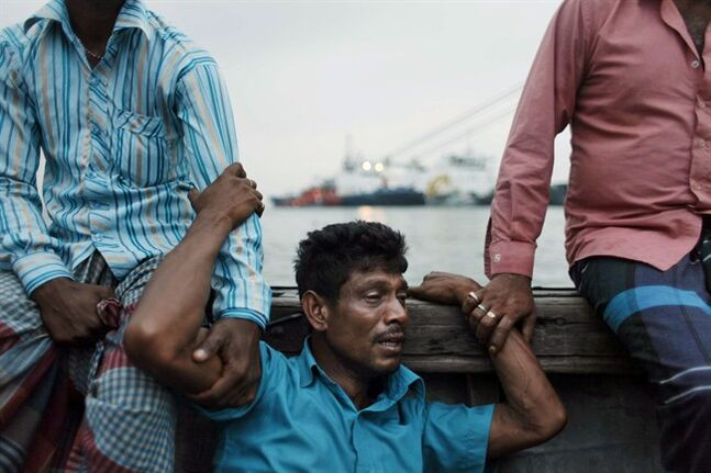A Bangladeshi man mourns for his missing brother, as rescuers continue to search the site of a ferry that sank, on the banks of the River Meghna in Munshiganj district, in Bangladesh, Friday, May 16, 2014. Rescuers have recovered at least 26 bodies after a ferry capsized during a storm in a river in central Bangladesh, officials said Friday. Police estimated at least 100 people were still missing, but there was no clear picture about exactly how many people were on board because the ferry operators did not maintain a passenger list, said a local administrator, Saiful Hasan. (AP Photo/Suvra Kanti Das)