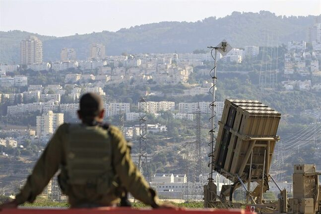 FILE - In this Aug. 28, 2013 file photo, an Israeli soldier is seen next to an Iron Dome rocket interceptor battery deployed near the northern Israeli city of Haifa. A state-owned Israeli arms company said it will unveil a new laser-defense system called the