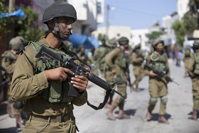 Israeli soldiers patrol during a search for three missing Israeli teenagers in the village of Taffouh near the West Bank city of Hebron, Wednesday, June 18, 2014. Israeli security forces searched the West Bank, looking for three missing teenagers, including an American, who they fear have been abducted by Palestinian militants. (AP Photo/Majdi Mohammed)