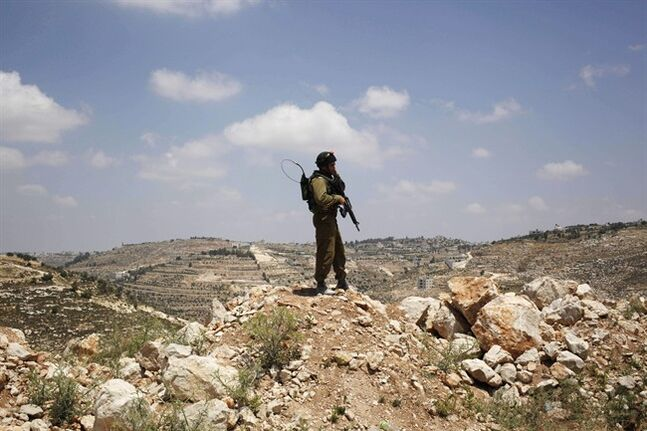An Israeli soldier stands near the West Bank city of Hebron, Friday, June 13, 2014. Israeli soldiers searched the West Bank on Friday for three missing teenagers from nearby settlements, one of them a U.S. citizen, amid fears Palestinian militants abducted them, authorities said. (AP Photo/Nasser Shiyoukhi)
