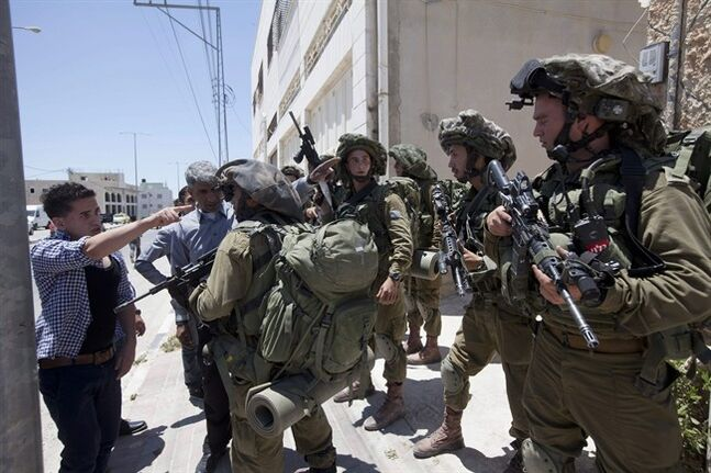 A Palestinian youth argues with Israeli soldiers as he tries to enter his home during a military operation to search for three missing teenagers outside the West Bank city of Hebron, Sunday, June 15, 2014. Israeli troops on Sunday arrested some 80 Palestinians, including dozens of members of Hamas, in an overnight raid in the West Bank as Prime Minister Benjamin Netanyahu accused the Islamic militant group of kidnapping three teenagers who went missing nearly three days ago. (AP Photo/Majdi Mohammed)