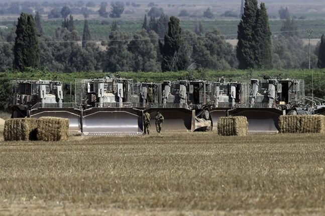 Israel military bulldozers are lined up near the Israeli and Gaza border Monday, July 7, 2014. The Islamic militant group Hamas that rules Gaza vowed revenge on Israel for the death of several of its members killed in an airstrike early Monday morning in the deadliest exchange of fire since the latest round of attacks began weeks ago. About a dozen rockets were fired at Israel from Gaza overnight the military said. (AP Photo/Tsafrir Abayov)