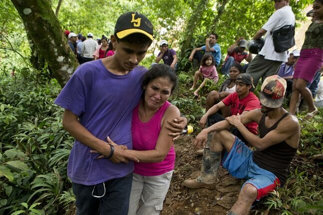Margarita Mendez, hugs her son while she cries and waits for news of her other son Salvador Urbina, one of the miners trapped at El Comal gold and silver mine after a landslide trapped at least 24 miners inside, in Bonanza, Nicaragua, Friday, Aug. 29, 2014. Rescuers on Friday located 20 of at least 24 gold miners trapped by a landslide in northern Nicaragua, but were not immediately able to bring them to safety. (AP Photo/Esteban Felix)